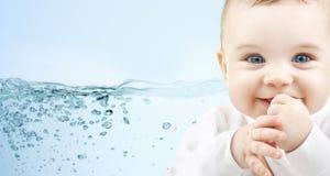 在蓝色背景的愉快的婴孩与水飞溅 免版税库存图片