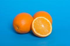 在蓝色背景的成熟桔子 半水多的桔子 库存照片