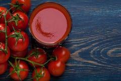 在蓝色背景的新鲜的西红柿汁 库存图片