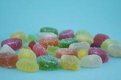 在蓝色背景的明亮的色的明胶糖果 在糖的橘子果酱 免版税库存照片