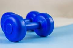在蓝色背景的明亮的蓝色哑铃 健康生活方式,丢失的体重的概念 免版税图库摄影