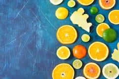 在蓝色背景的柑橘样式与拷贝空间 被分类的柑橘水果 切片桔子、蜜桔、柠檬、石灰和姜  库存图片