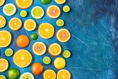 在蓝色背景的柑橘样式与拷贝空间 被分类的柑橘水果 切片桔子,蜜桔,柠檬,石灰 顶视图 免版税库存照片