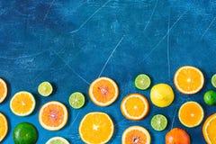 在蓝色背景的柑橘样式与拷贝空间 被分类的柑橘水果 切片桔子,蜜桔,柠檬,石灰 顶视图 免版税库存图片