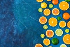 在蓝色背景的柑橘样式与拷贝空间 被分类的柑橘水果 切片桔子,蜜桔,柠檬,石灰 顶视图 库存图片