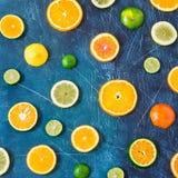 在蓝色背景的柑橘样式 被分类的柑橘水果 切片桔子,蜜桔,柠檬,石灰 顶视图 正方形 库存图片