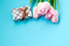 在蓝色背景的桃红色郁金香与礼物盒 平的位置,顶视图 背景能明信片使用的华伦泰 图库摄影