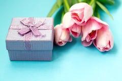 在蓝色背景的桃红色郁金香与礼物盒 平的位置,顶视图 背景能明信片使用的华伦泰 库存图片