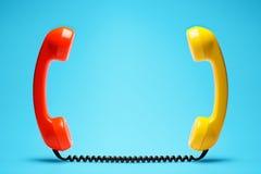 在蓝色背景的橙色和黄色电话 免版税库存照片