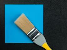在蓝色背景的油漆刷 库存照片