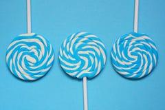 在蓝色背景的白色和蓝色棒棒糖 免版税库存照片