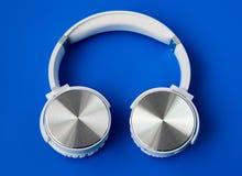在蓝色背景的白色无线bluetooth耳机 库存图片