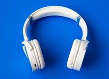 在蓝色背景的白色无线bluetooth耳机 库存照片