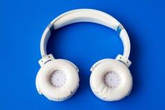 在蓝色背景的白色无线bluetooth耳机 免版税库存照片