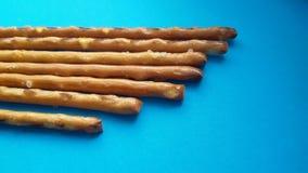 在蓝色背景的盐味的椒盐脆饼棍子 嘎吱咬嚼和美味! 库存图片