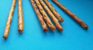 在蓝色背景的盐味的椒盐脆饼棍子 嘎吱咬嚼和美味! 免版税库存图片