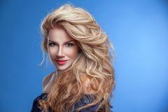 在蓝色背景的秀丽女孩华美的头发画象在牛仔布 免版税库存图片