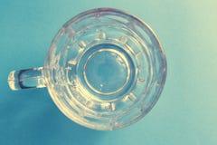 在蓝色背景的空和透明玻璃啤酒瓶子 免版税图库摄影
