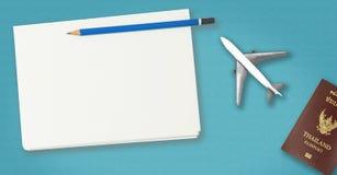 在蓝色背景的空白的旅行笔记本与飞机和护照 库存照片