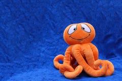 在蓝色背景的章鱼玩具 免版税图库摄影