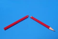 在蓝色背景的红色和残破的铅笔 免版税库存图片