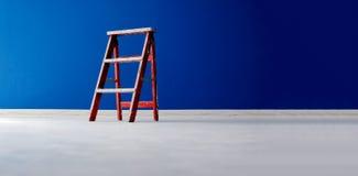 在蓝色背景的红色木梯子 库存图片