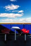 在蓝色背景的红色椅子在轮渡在春天 免版税库存照片