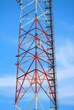 在蓝色背景的红色白色黑传输塔 库存图片