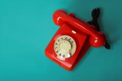 在蓝色背景的红色葡萄酒电话 库存照片