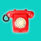 在蓝色背景的红色葡萄酒电话 库存图片
