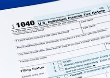 1040在蓝色背景的纳税申报形式 库存图片