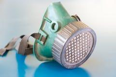在蓝色背景的肮脏的呼吸道防护 免版税库存照片