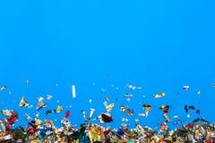 在蓝色背景的色的五彩纸屑飞行 库存图片