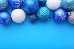 在蓝色背景的蓝色和银色圣诞节球 免版税库存照片
