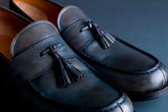 在蓝色背景的蓝色游手好闲者鞋子 一个对 关闭 库存照片