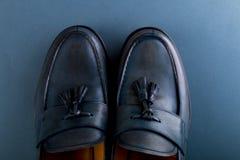 在蓝色背景的蓝色游手好闲者鞋子 一个对 顶视图 复制空间 免版税库存照片