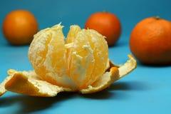 在蓝色背景的被剥皮的成熟蜜桔用橙色蜜桔 图库摄影