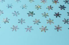 在蓝色背景的许多闪烁雪花 免版税库存图片