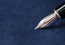 在蓝色背景的钢笔与裁减路线 免版税库存照片