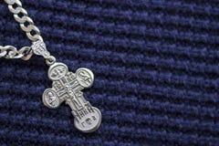 在蓝色背景的银色十字架 信念的符号 基督教 图库摄影