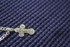 在蓝色背景的银色十字架 信念的符号 基督教 免版税库存照片