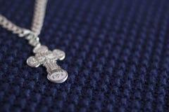 在蓝色背景的银色十字架 信念的符号 基督教 库存图片