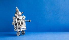 在蓝色背景的银色金属机器人 两个与天线的轮子家仆机器人字符 创造性的设计 图库摄影