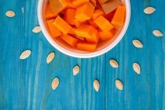 在蓝色背景的鲜美南瓜 在倾吐的餐馆沙拉的主厨概念食物新鲜的厨房油橄榄 免版税库存图片