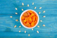 在蓝色背景的鲜美南瓜 在倾吐的餐馆沙拉的主厨概念食物新鲜的厨房油橄榄 库存图片