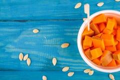 在蓝色背景的鲜美南瓜 在倾吐的餐馆沙拉的主厨概念食物新鲜的厨房油橄榄 免版税图库摄影