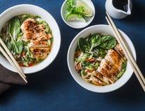 在蓝色背景的鸡、面条和菜亚洲样式汤 免版税库存图片