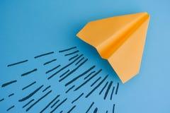 在蓝色背景的黄色纸飞机 库存图片