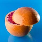 在蓝色背景的整个slicend葡萄柚,方形的射击 免版税图库摄影