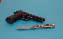 在蓝色背景的黑手枪和铁刀子 库存照片